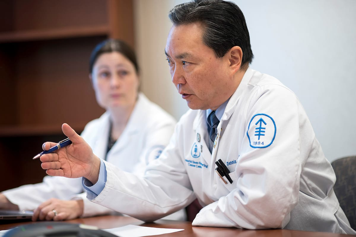 MSK Surgeon in white lab coat sitting in profile (facing left) talking and gesturing.