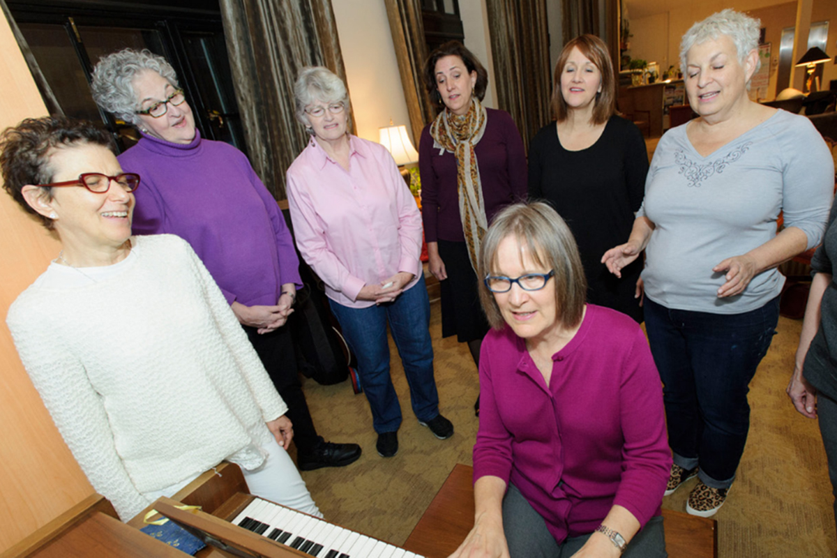 Women sing at a piano