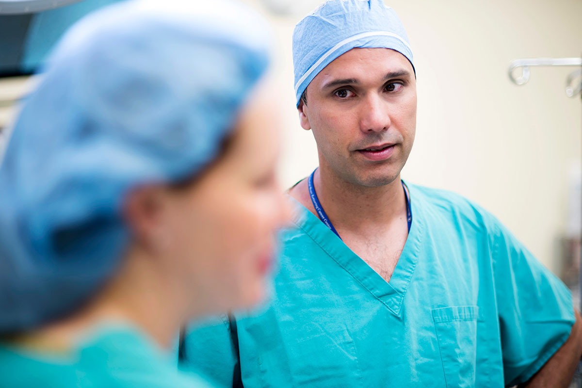 MSK surgeon, Oliver Zivanovic, speaking with a female colleague dressed in their scrubs.