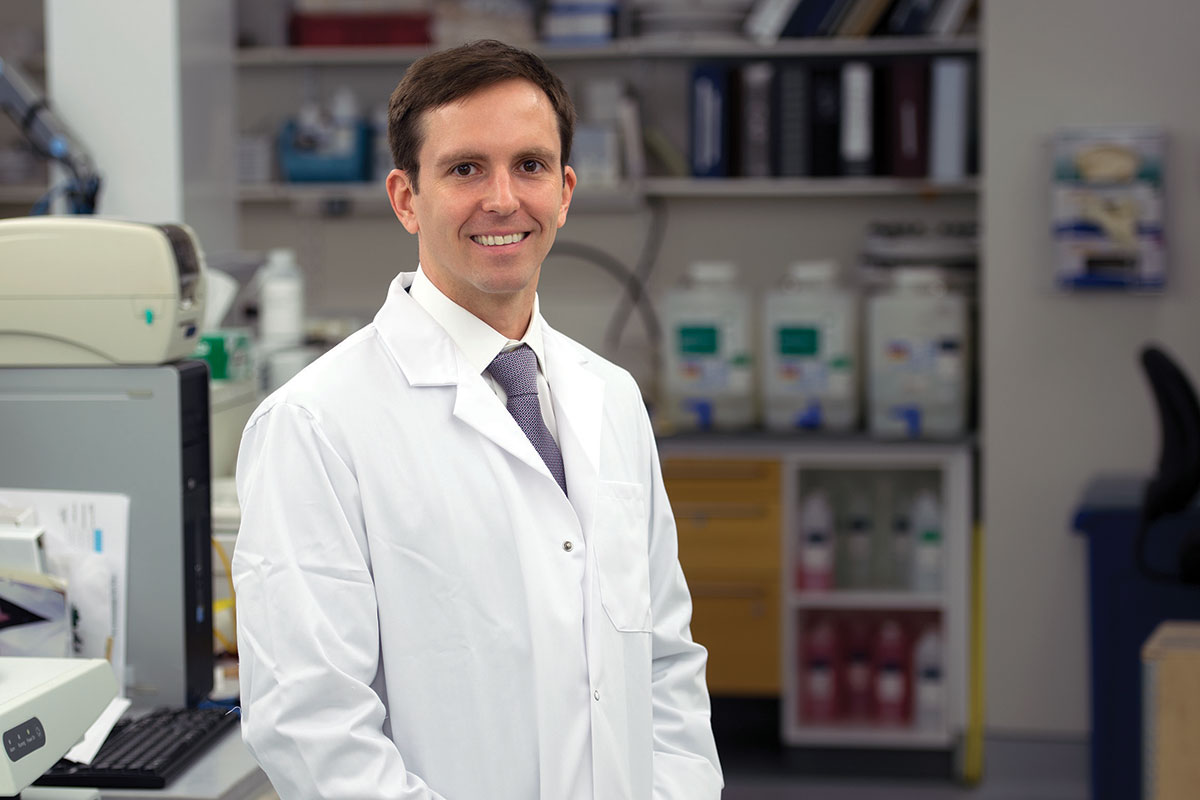Travis Hollmann in a white coat in his laboratory