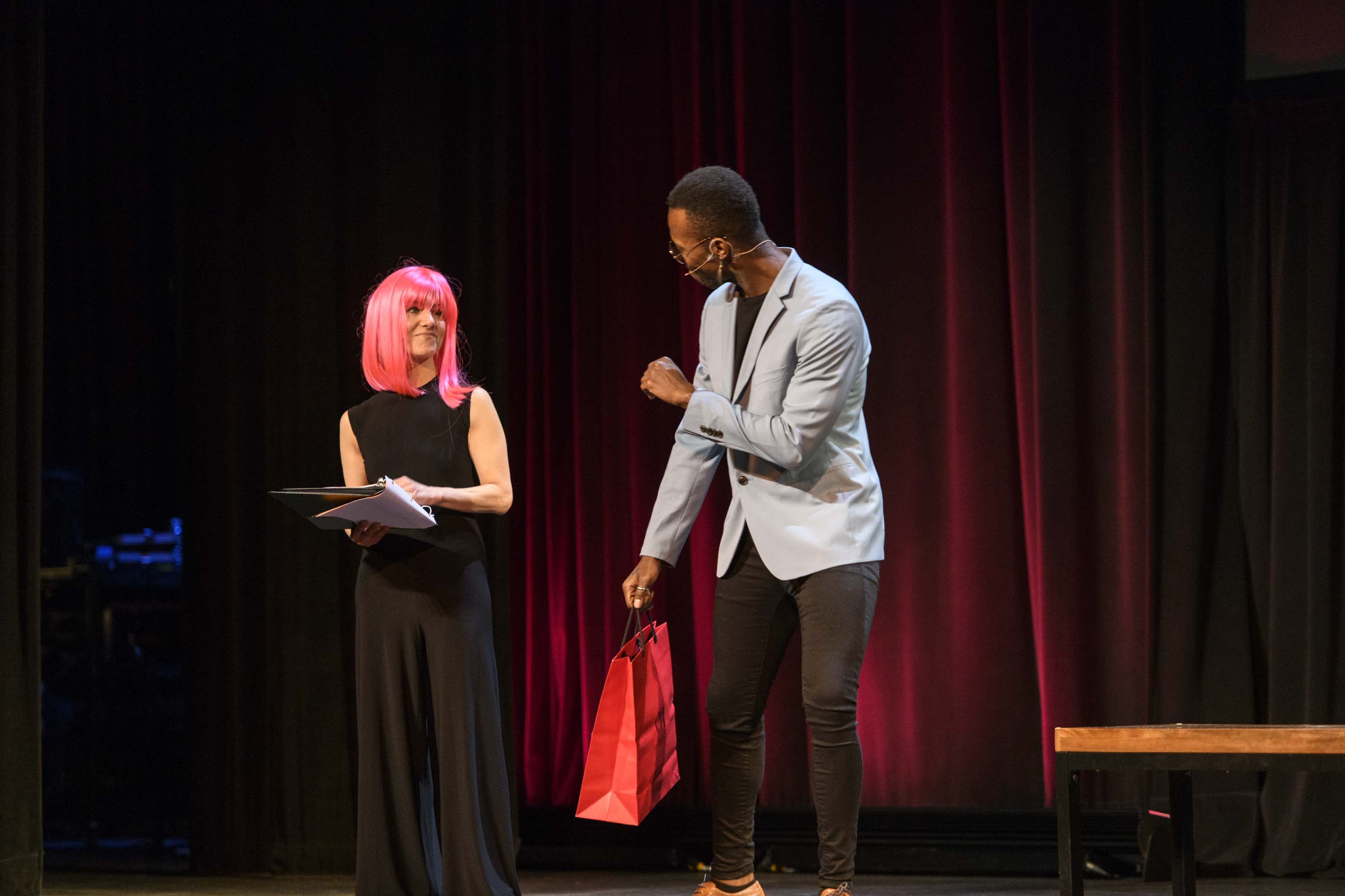 Woman in pink wig talks to man on stage