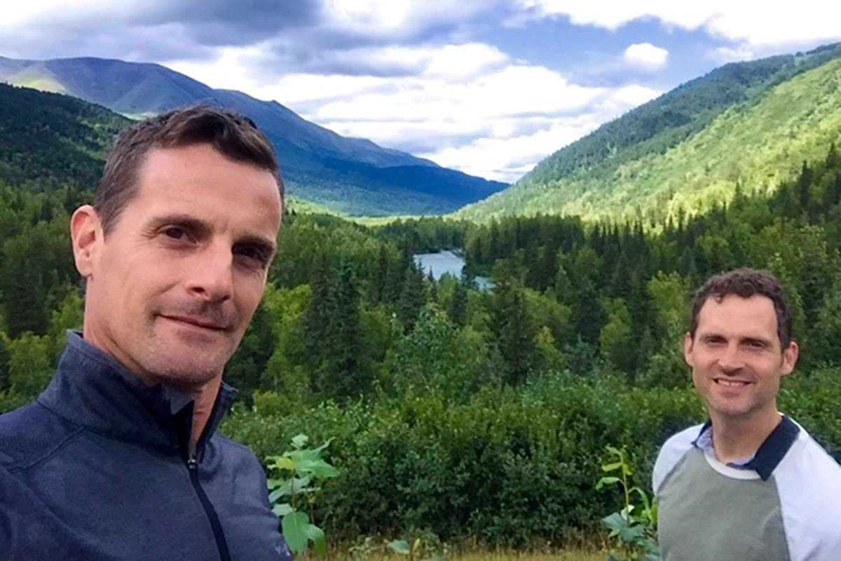 MSK patient Mark McIntosh and his husband, Edgar, posing in front of grassy mountains