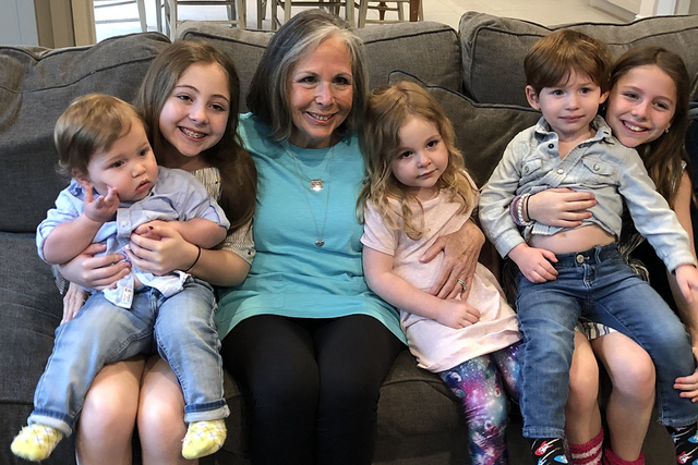 Lynne sitting on a couch, holding her grandchildren