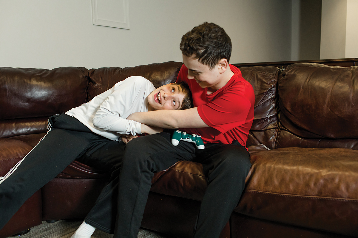 Two boys play on a couch