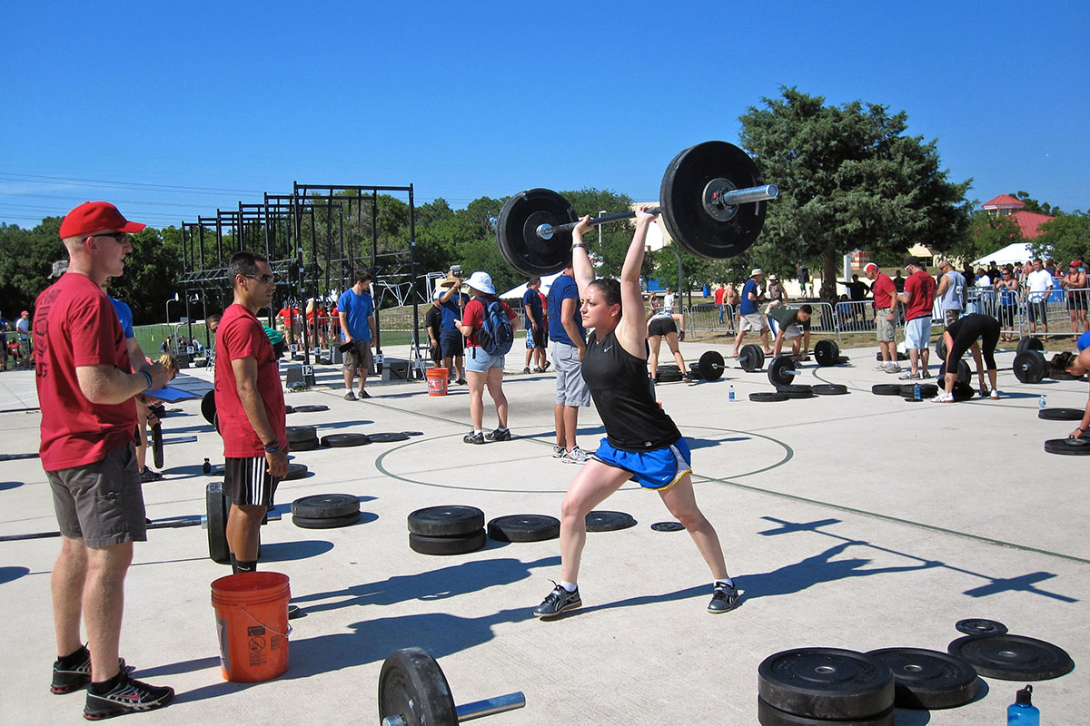 Physician-scientist Allison Betof Warner lifts a barbell at a CrossFit competition.
