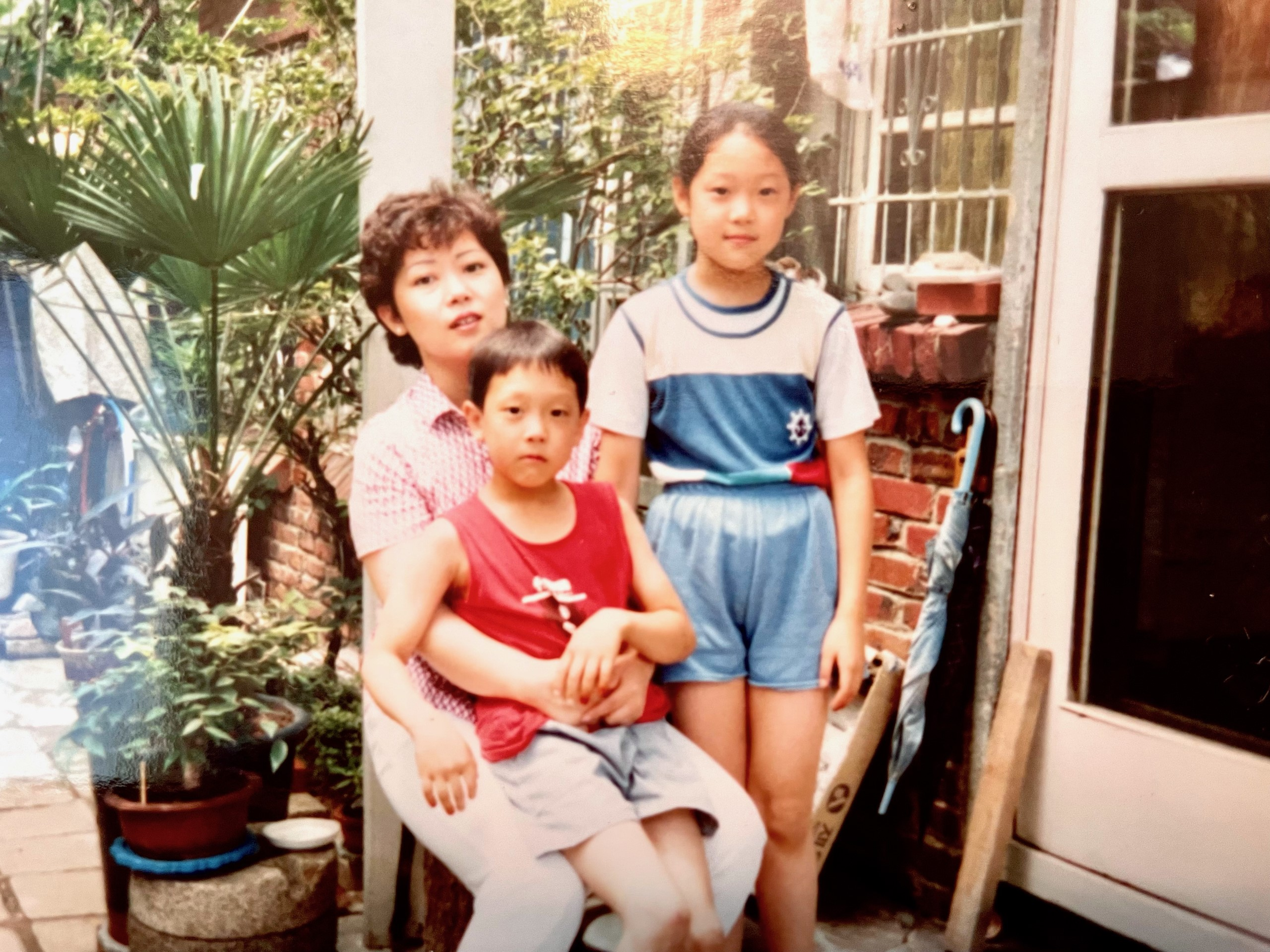 Young boy and girl with their mother, sitting on a chair