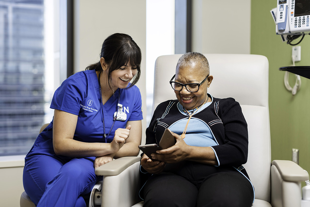 A registered nurse shares a laugh in an exam room with a patient as they both look at a cell phone screen.