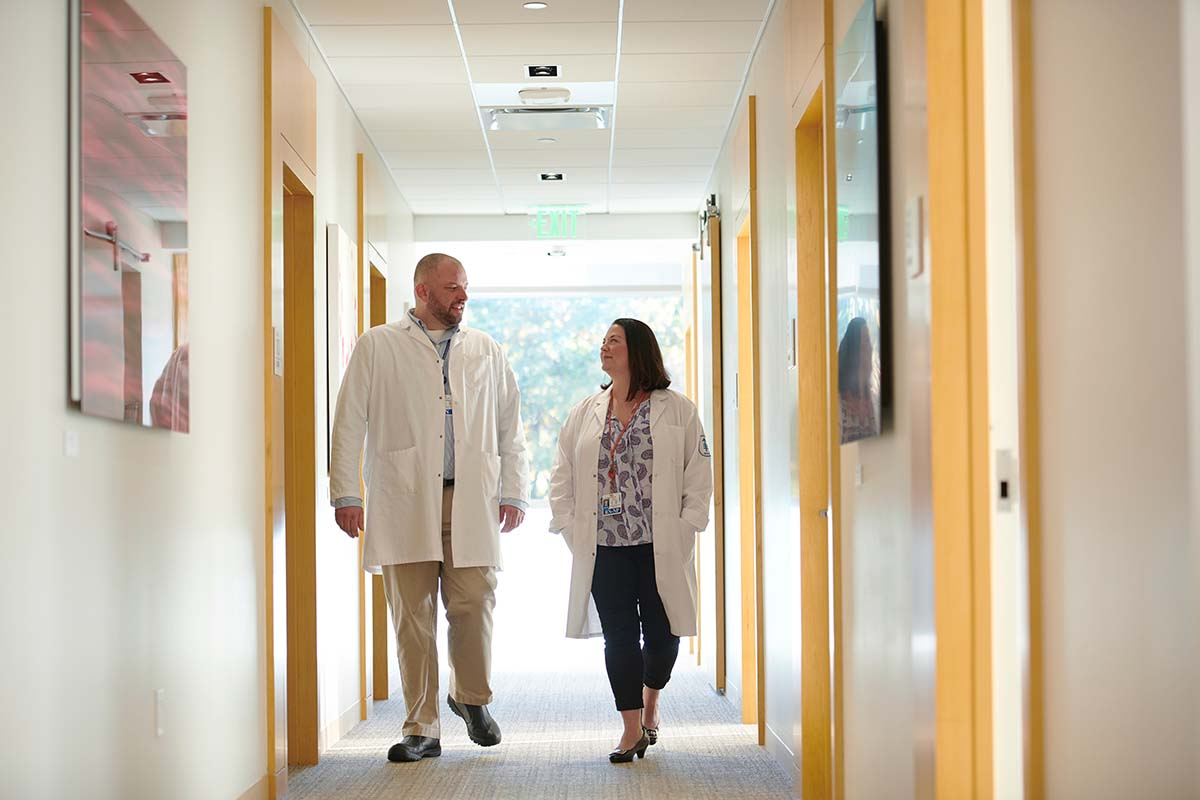Nurse Bryon Wanderer and nurse practitioner Erin Scansarole walking in the hall