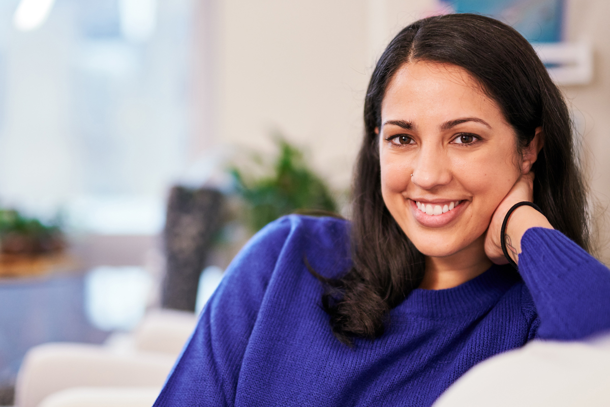 Woman smiling wearing a purple sweater