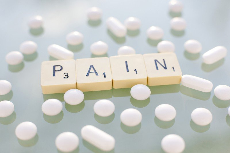 Four scrabble tiles spelling out pain surrounded by numerous white pills (round and oblong) representing painkillers.