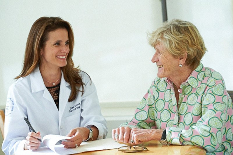 Zana Correa, a nurse practitioner in the survivorship clinic at MSK, speaks with a female patient.