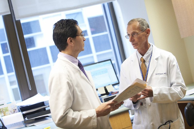 MSK medical oncologists Leonard Saltz (left) and David Paul Kelsen (right) speak to each other in an office.