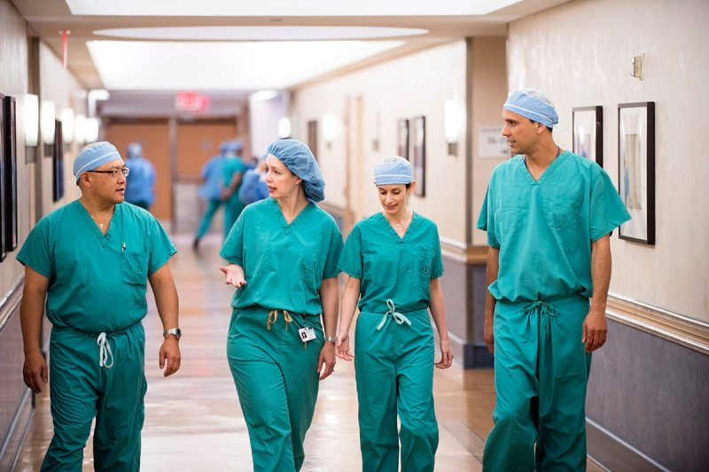 Four ovarian cancer surgeons in scrubs walking down hallway toward camera conversing with each other.