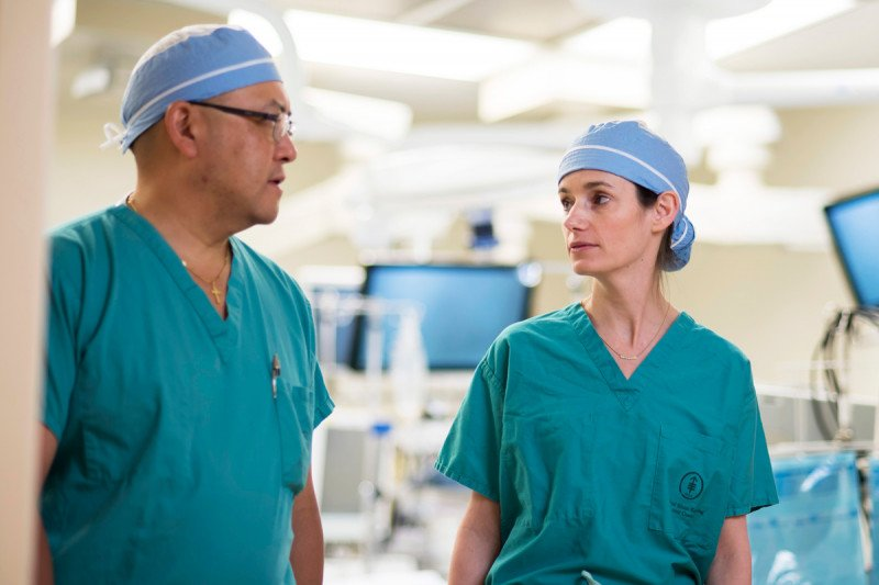 MSK gynecologic surgeons Yukio Sonada and Kara Long Roche speak to each other dressed in their scrubs.