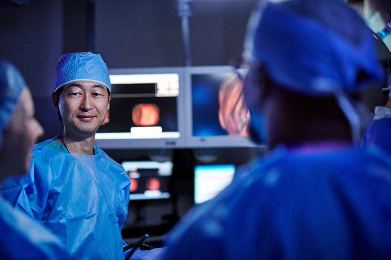 MSK gastroenterologist, Makoto Nishimura, speaks with his colleagues before a procedure dressed in their scrubs.