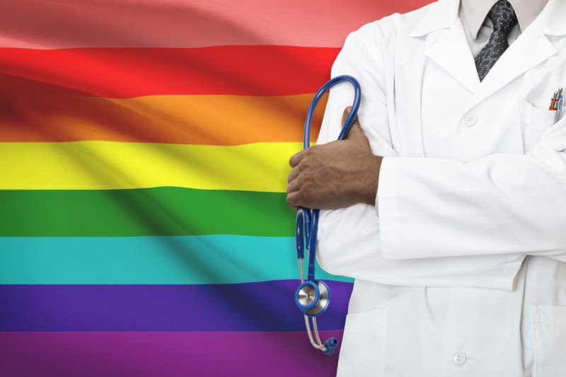 Doctor standing in front of a rainbow flag