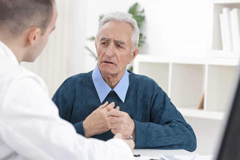 Older man talking with a doctor about esophageal cancer.