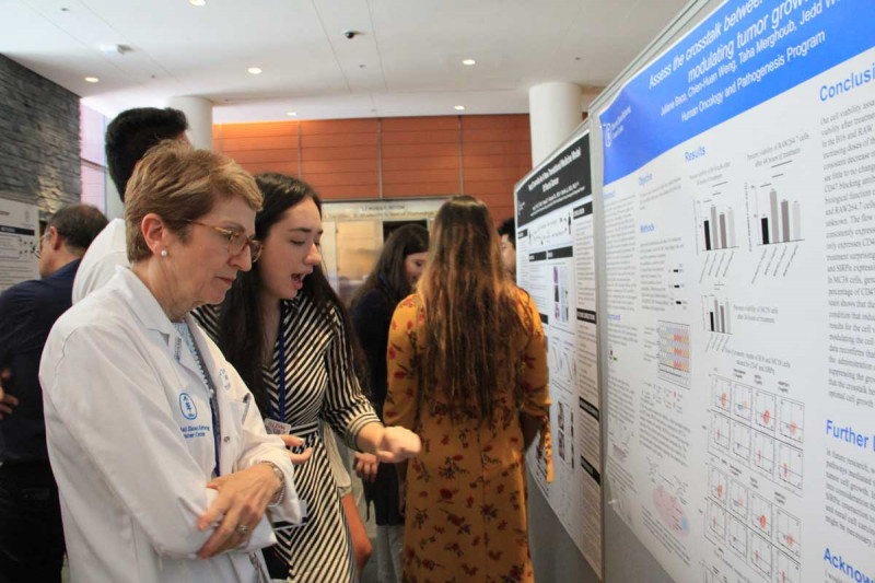 Physician-In-Chief, Dr. Lisa DeAngelis reviews Juliane Baco's research poster