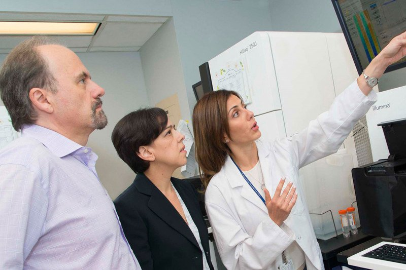 Three scientists look up at ascreen showing genetic information about a tumor.