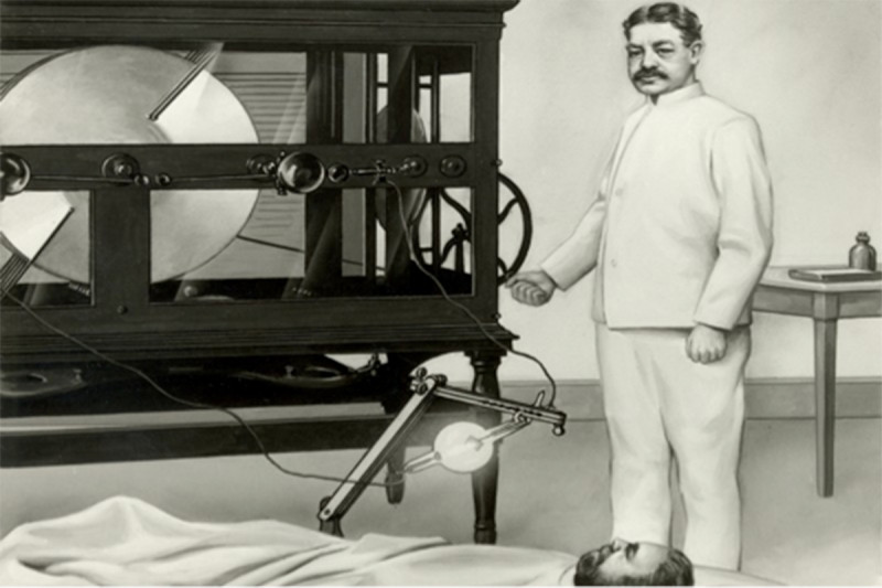 William Coley administers radiation to a patient with one of the first x-ray machines.