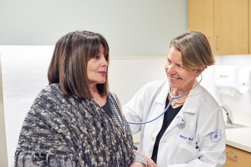 Female doctor in white coat examining patient with stethoscope.