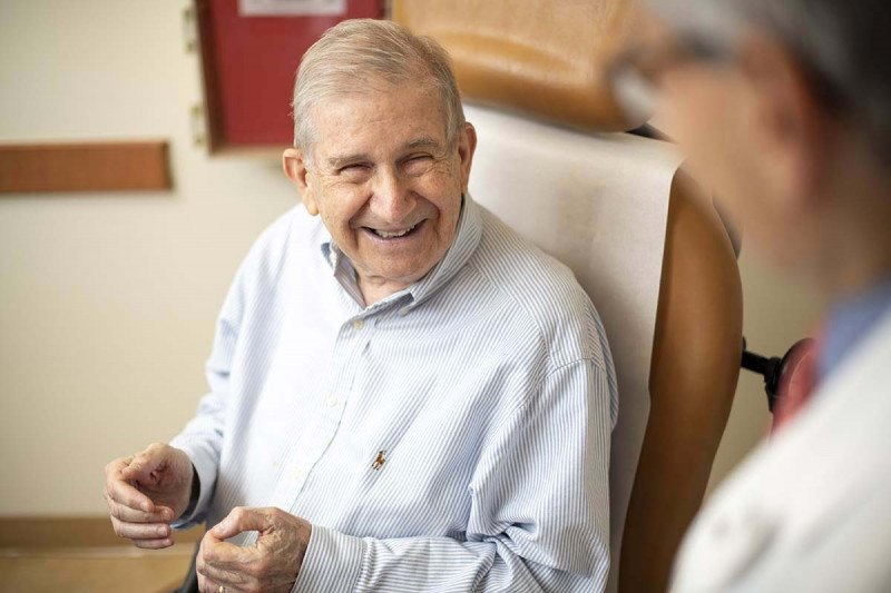 Smiling elderly man sitting in chair.