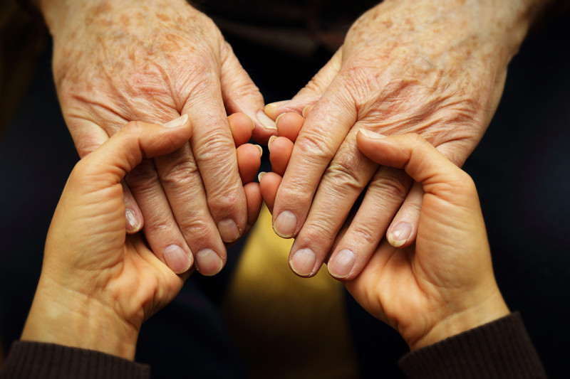 Young hands holding the hands of an older adult