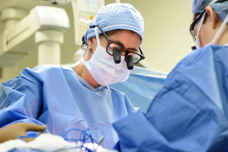 Surgeon in scrubs operating on patient.