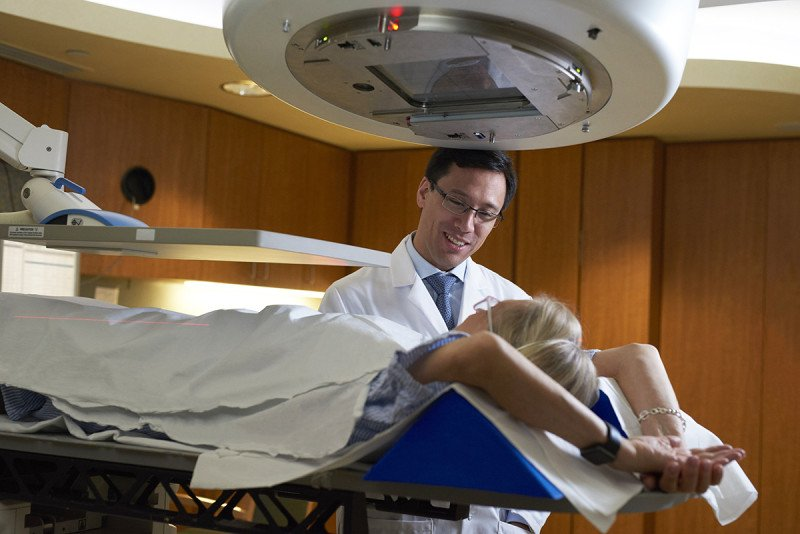 Doctor in white coat standing next to treatment table with patient lying on her back underneath radiation devices.