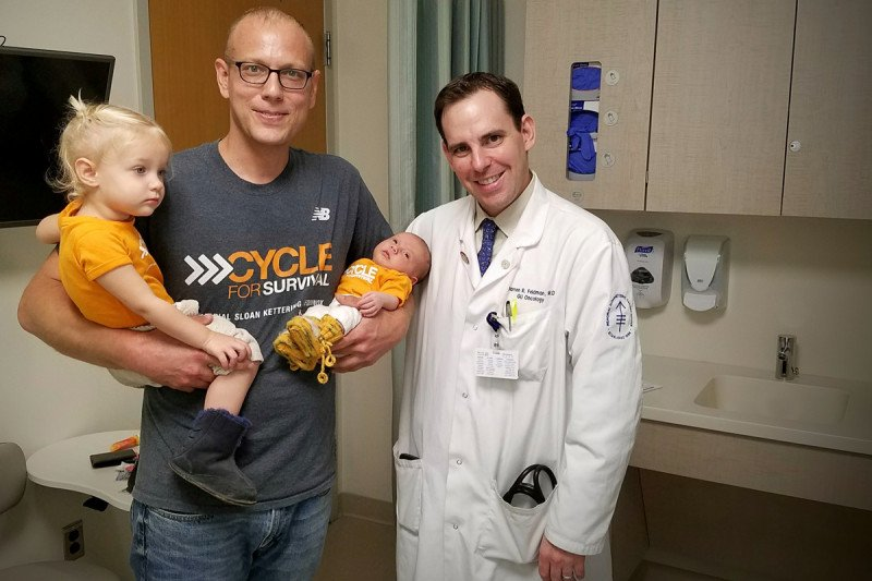 Memorial Sloan Kettering patient Jay Erickson poses with his two daughters and his MSK physician, Darren Feldman
