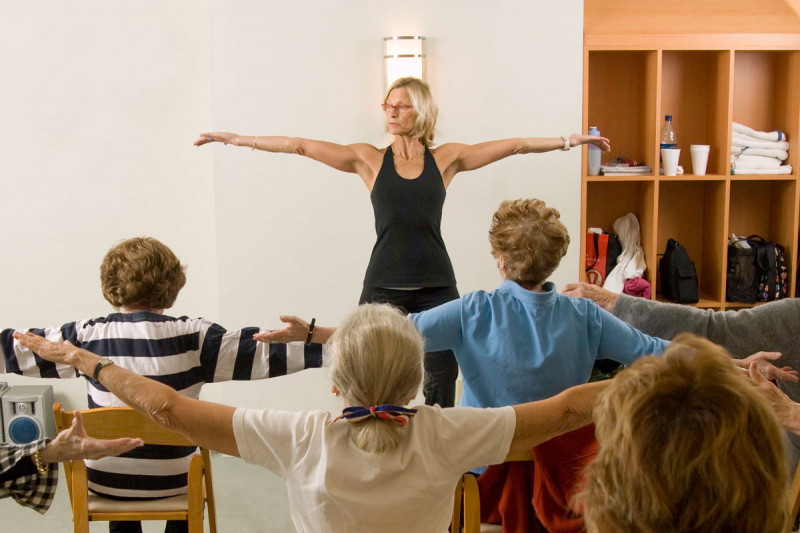 "Female instructor leading a ""chair yoga"" class with female patients seated with back to camera and arms stretched to side."