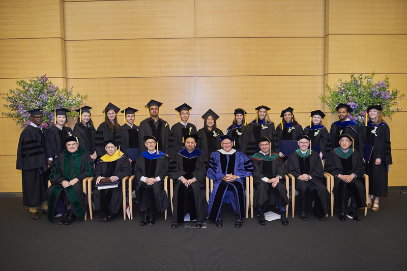 Graduates and speakers pose on a stage