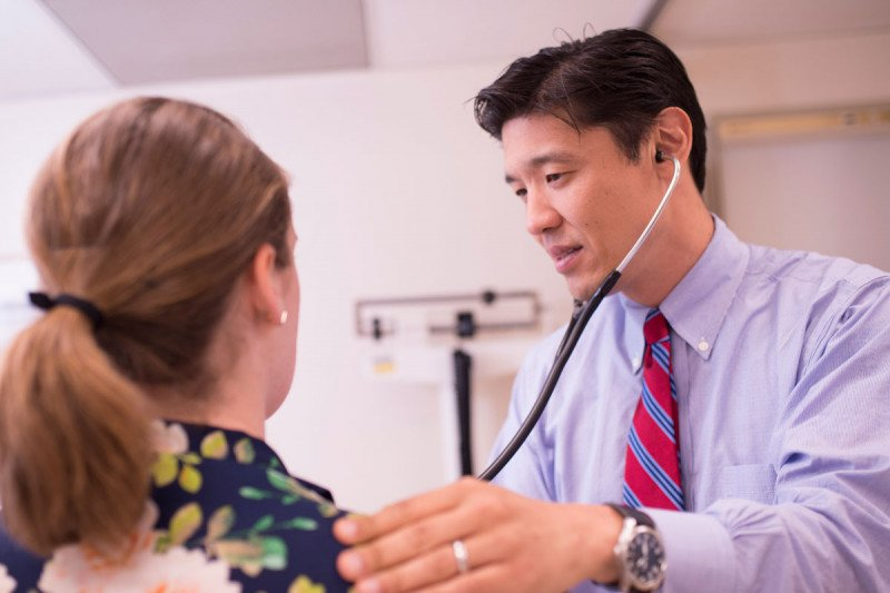 Memorial Sloan Kettering salivary gland cancer doctor, Alan Ho, examines a female patient using his stethoscope.