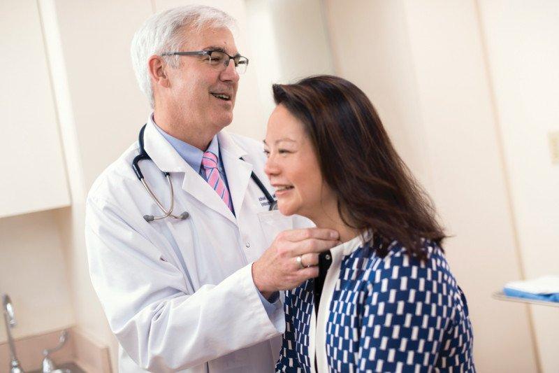 Doctor Michael Tuttle in white coat examining female patient.