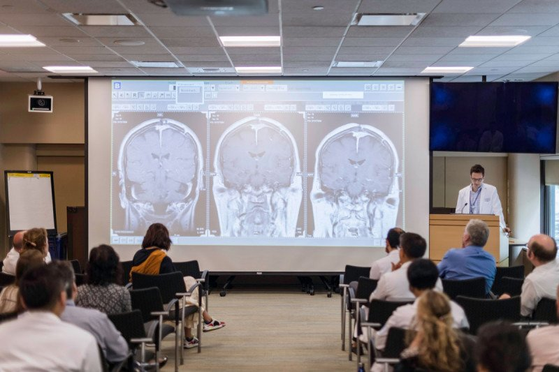 MSK doctor sharing large projector screen showing three brain scans to a room full of experts.
