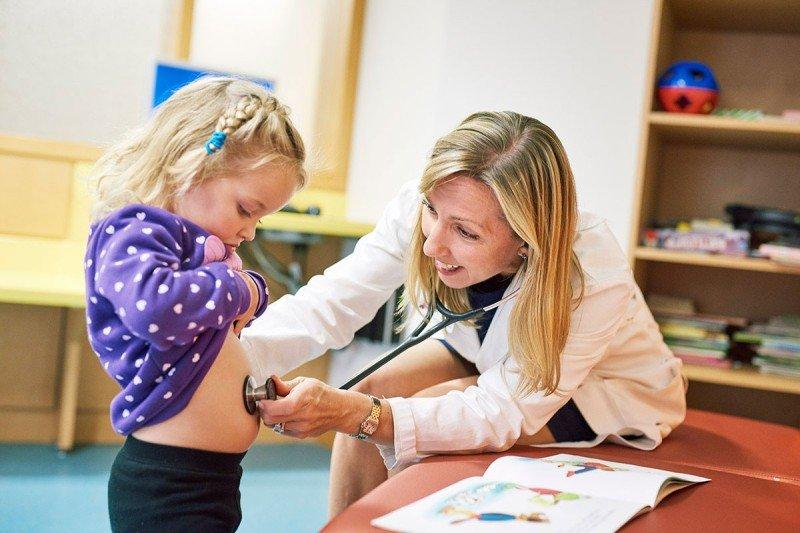 Smiling female physician, sitting on right, holding stethoscope against abdomen of blond girl