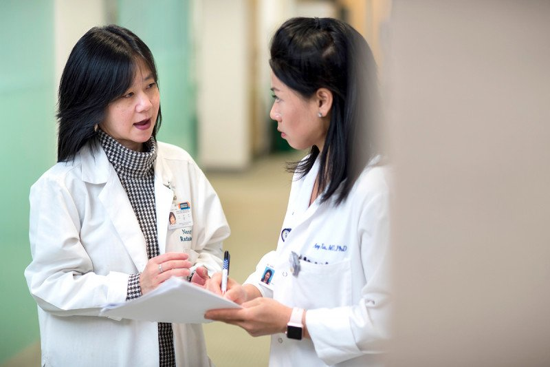 MSK head and neck radiation oncologist,  Nancy Lee, speaking with another doctor who is taking notes.