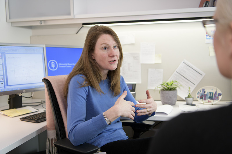 Woman sitting at her desk explaining something to someone off camera