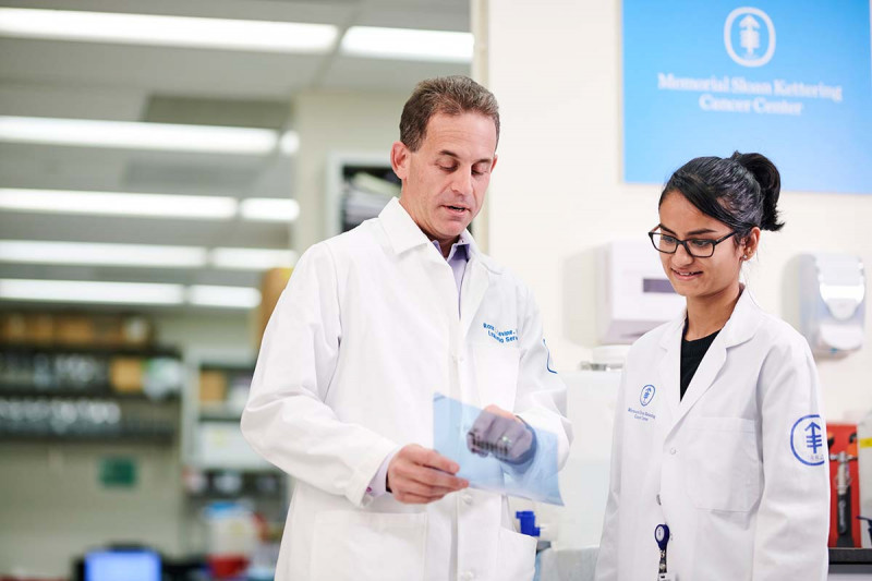 Physician-scientist Ross Levine and research technician Aishwarya Krishnan speak in the lab