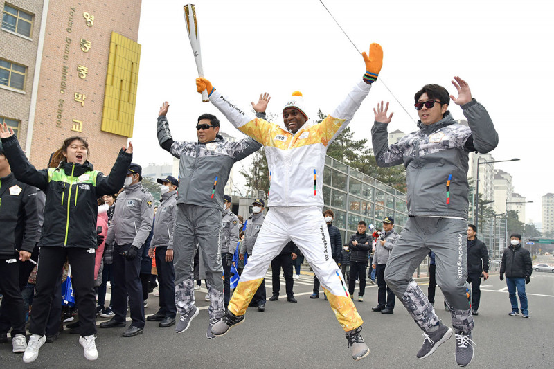 Seun jumping while holding the Olympic torch