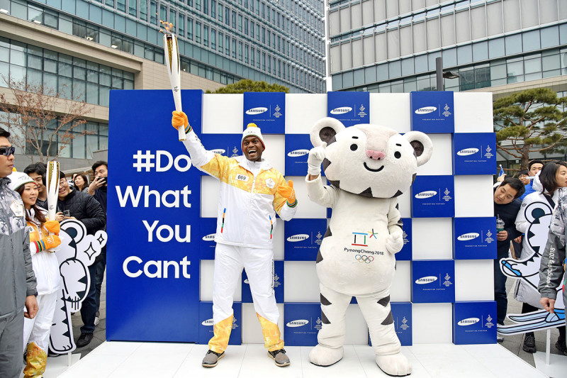 Seun standing holding the torch with Olympic mascot