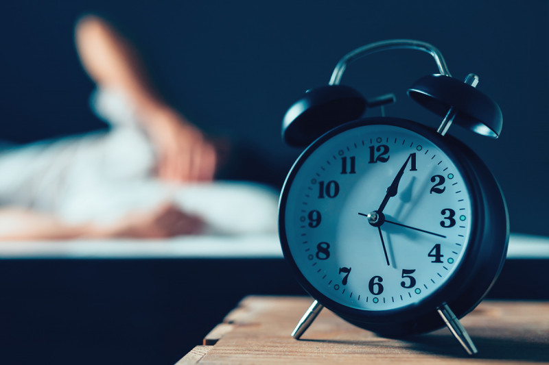 Alarm clock in foreground with person (out of focus) in bed in the background.