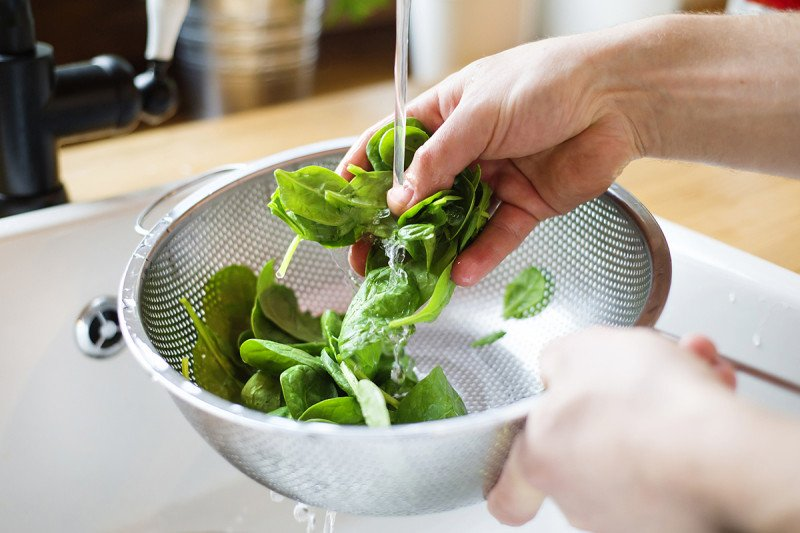 Man's hands washing salad greens in a sink