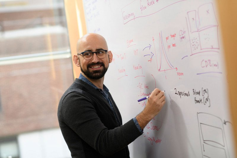 Bioinformatician Ahmet Zehir stands at a whiteboard