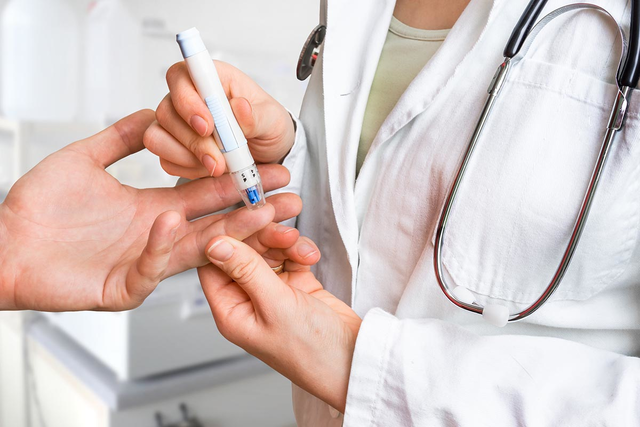 Doctor pricks finger of patient with diabetes