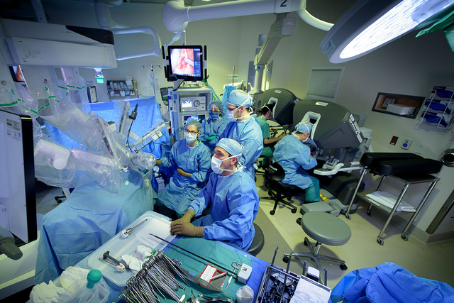 MSK surgeons gathered around a robot used for cancer surgery
