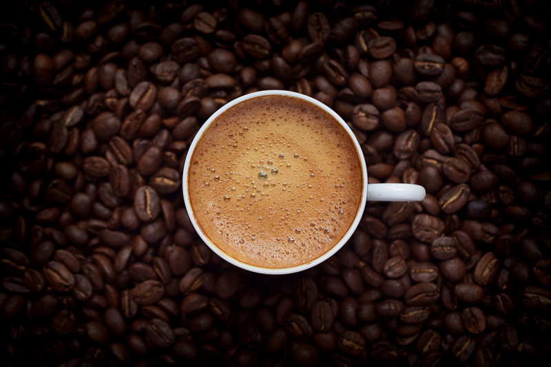 coffee cup surrounded by beans