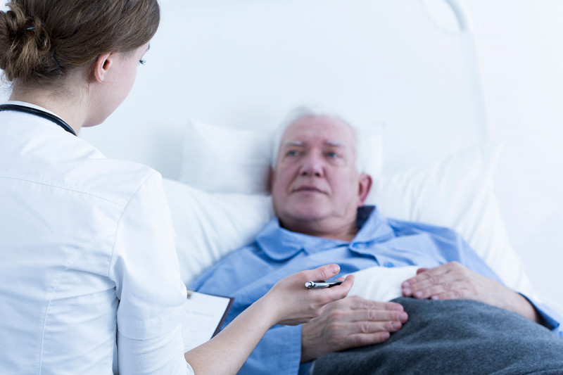 Old man lying in hospital bed being spoken to by nurse