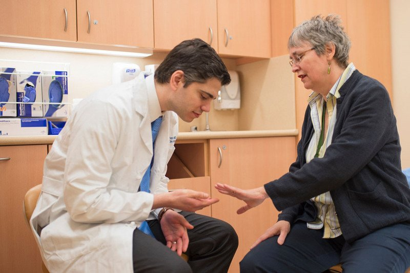 MSK Medical Oncologist, David Hyman, examining female patient's hand for Erdheim-Chester disease.