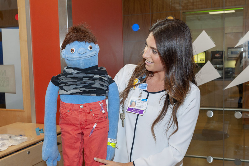 Child life therapist Monica Slodowski gives a hand to Kurt, a puppet that introduces children to what they can expect from treatment.